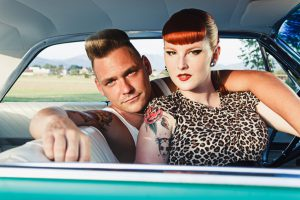Rockabilly couple sitting in a car. Outdoor photography.