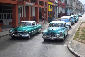Havana, Cuba, January 18th, 2016: Classic American cars driving on the street. The old-styled American vehicles from 50s are the one of the most popular cars in Cuba.